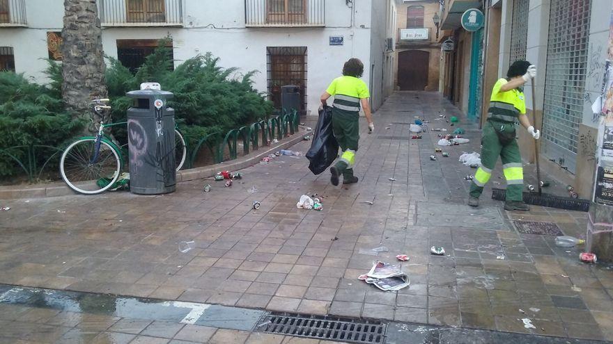 Treballadores municipals netegen les restes d'un botellot al barri de Benimaclet (València)