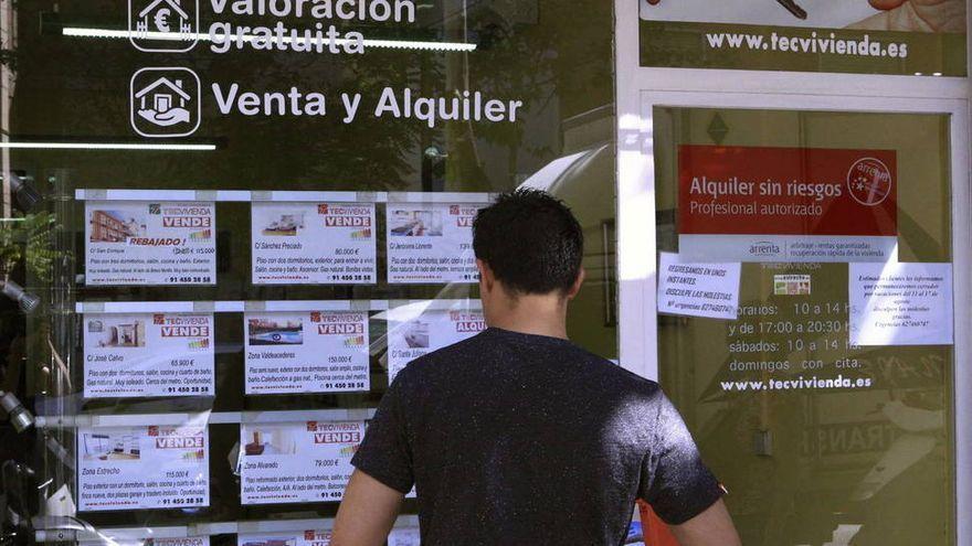 Un home mira l'aparador d'una immobiliària en una imatge d'arxiu