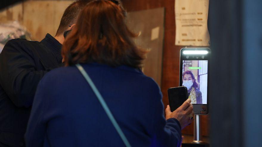 Una treballadora mostra a Roma el certificat de vacunació a l'entrada al treball
