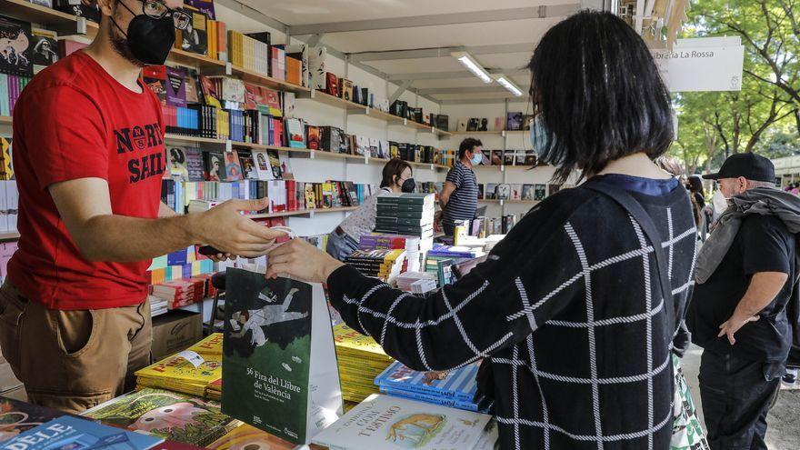 Una xica compra un llibre en la 56a edició de la Fira del Llibre de València