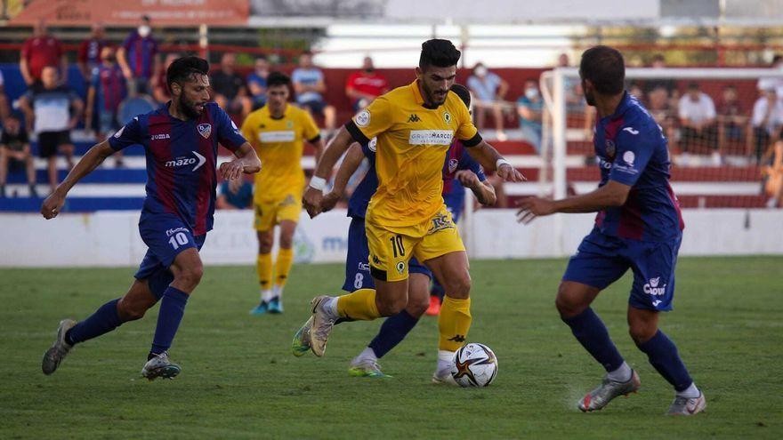 Un jugador de l'Hèrcules avança amb el baló sota la mirada dels jugadors de l'Alzira