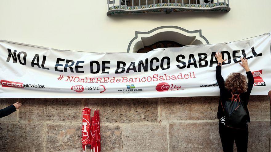Una persona penja una pancarta en la façana del Banc Sabadell a València