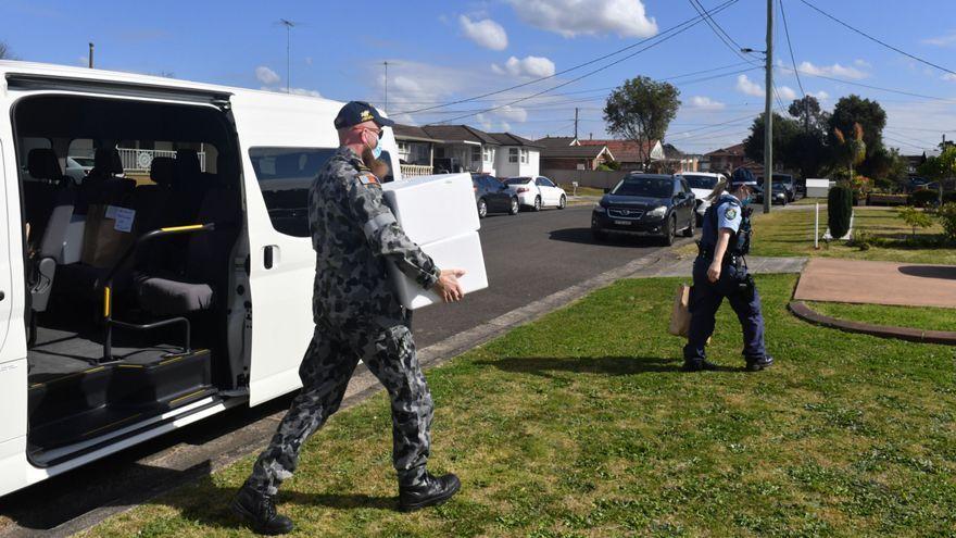 Un soldat trasllada unes caixes, al costat d'una agent de policia, pels carrers de la regió de Sydney