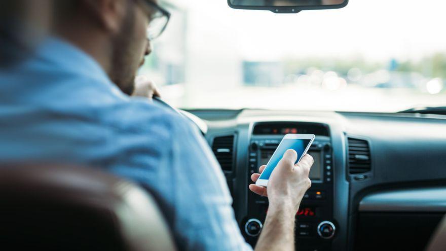 Un conductor mira el seu telèfon mòbil