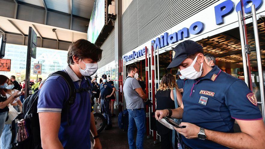 Un policia revisa el certificat Covid d'un passatger abans d'entrar a l'estació de Milà