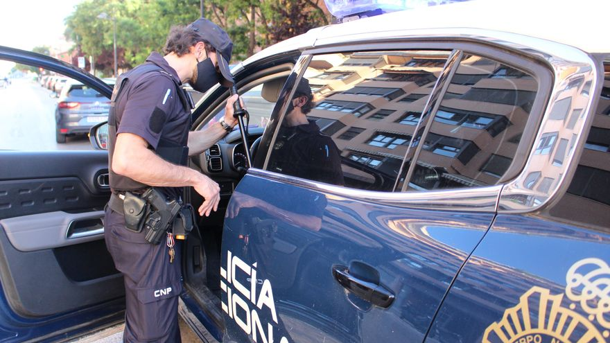 Un agent de la Policia Nacional al costat del seu cotxe patrulla