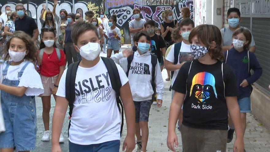 Nombrosos escolars es dirigeixen a l'escola amb la mascareta posada per a evitar contagis
