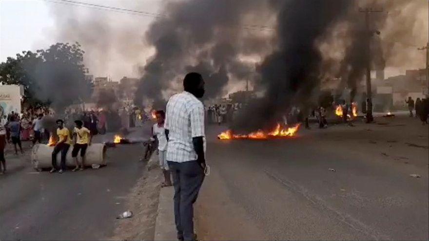 Diverses persones als carrers de Khartum, la capital del Sudan, on ja es veuen pneumàtics cremats