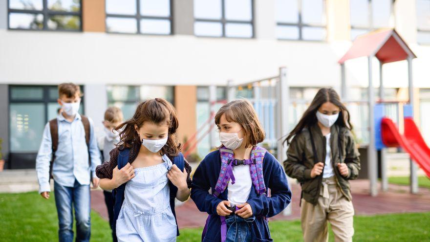 Un grup de xiquets i xiquetes, amb mascareta al pati de l'escola