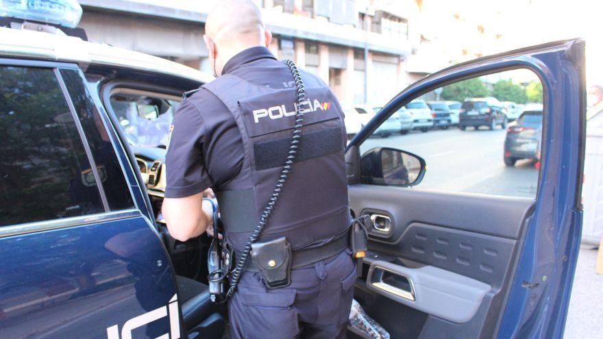 Un agent de la Policia Nacional amb un cotxe patrulla, en una imatge d'arxiu