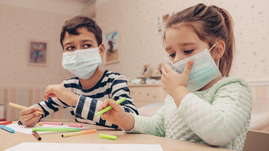 Dos xiquets amb mascareta fan quarantena a casa, en una imatge d'arxiu