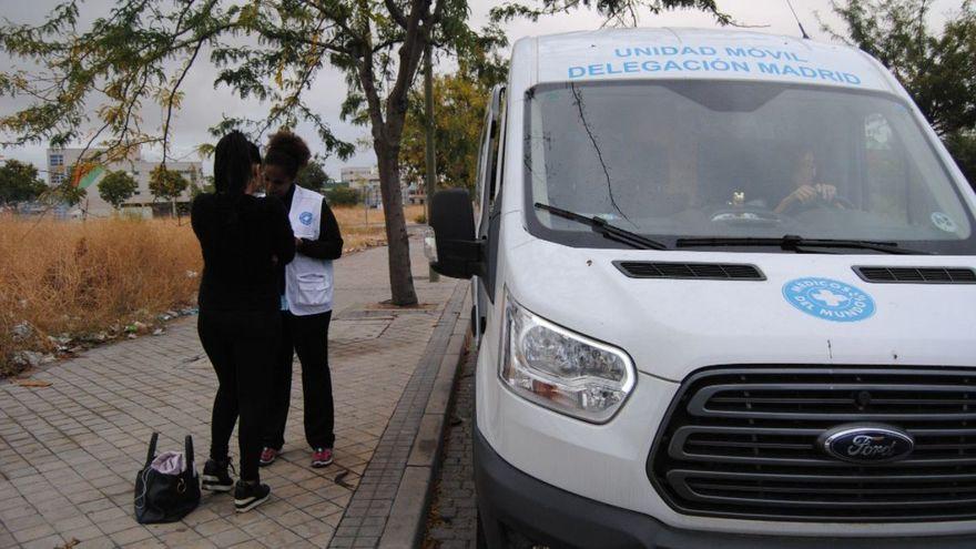 Una tècnica de Metges del Món parla en una dona en una via pública de la comunitat de Madrid
