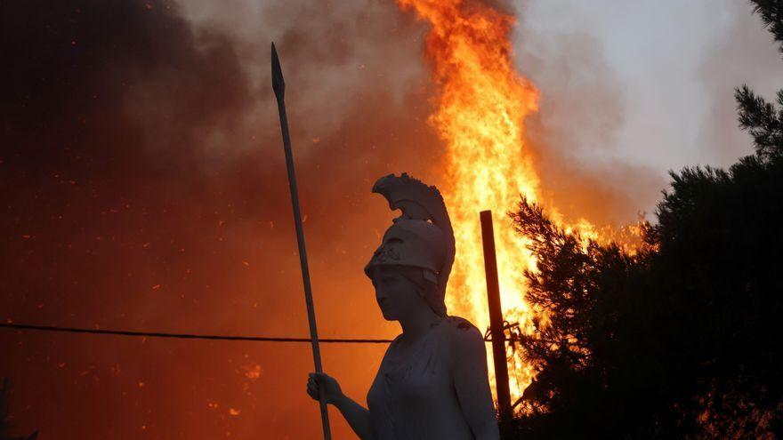 Una estàtua de la deesa Atena amb les flames del suburbi de Varibombi de fons
